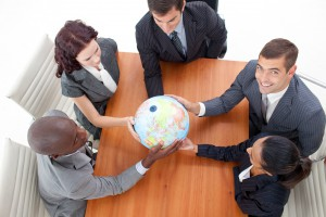 High Angle of businessteam holding a globe in a meeting and businessman smiling upwards. Global business